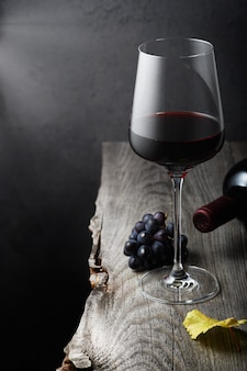 Glass of red wine close up on an old wooden table