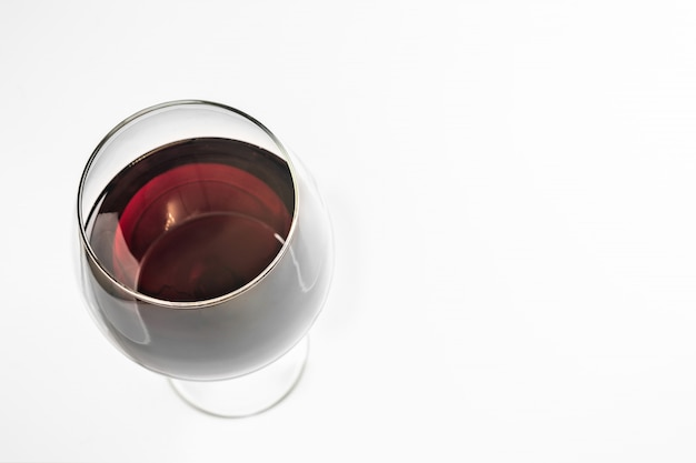 Glass of red wine, copy space, isolated. spanish emerald wine in a glass with a high stem.