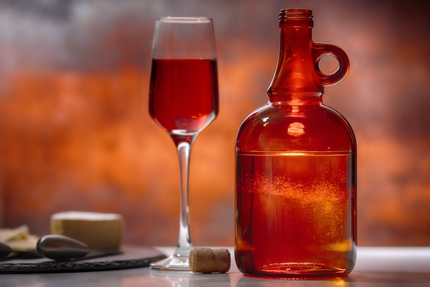 Glass of red wine, decanter and cheese board on a bar or tavern counter