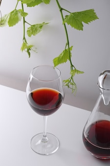 A glass of red wine and a decanter on a white table. light background.