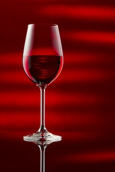A glass of red wine on a glossy table.