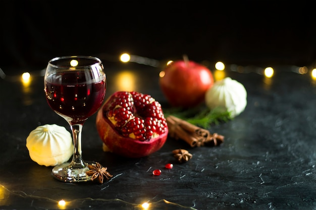 A glass of red wine a large pomegranate a marshmallow a garland concept of still life and holidays new year or christmas