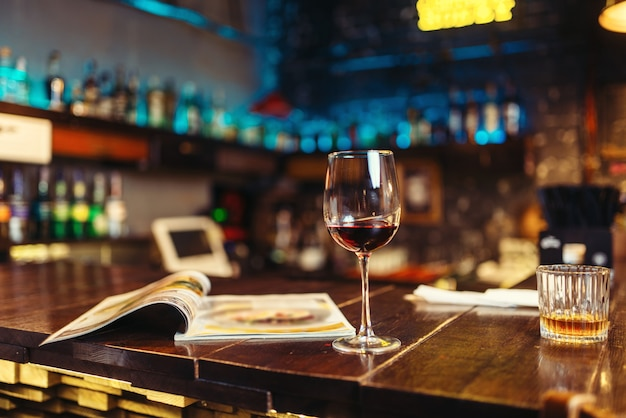 Glass of red wine and opened menu on wooden bar counter. night lifestyle concept