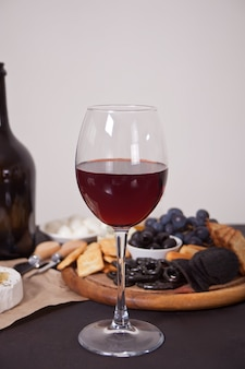 Glass of red wine and plate with assorted cheese, fruit and other snacks for party