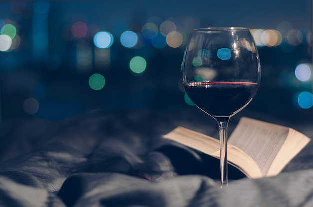 Glass of red wine put on bed with book