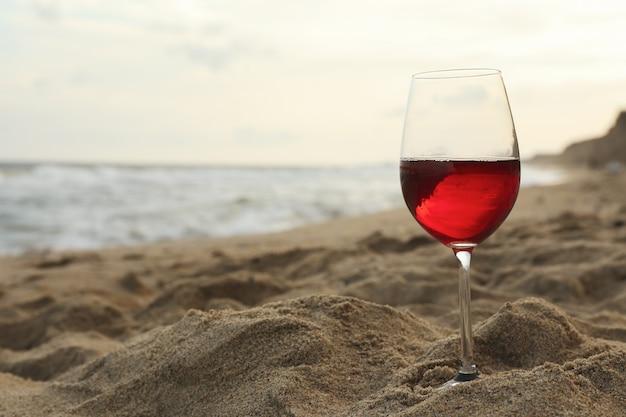 Glass of red wine on sandy sea beach