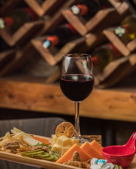 Glass of red wine served with cheese plate
