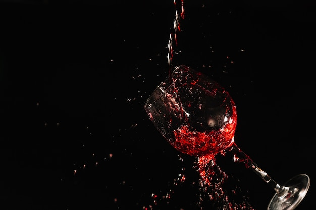 Glass of red wine splashing on black background