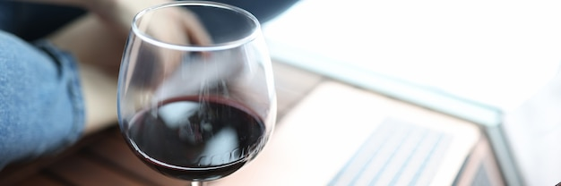 Glass of red wine stands on floor next to man sits in background