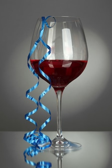 Glass of red wine and streamer after party on gray background