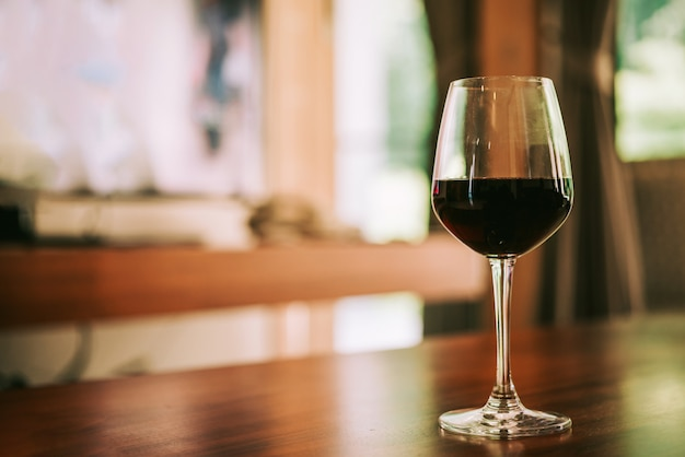 Glass of red wine on table in house