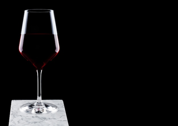 Glass of red wine on white marble board on black background.