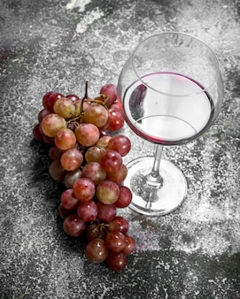 Glass of red wine with a branch of fresh grapes. on a rustic background.