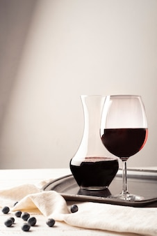 Glass of red wine with carafe on a tray