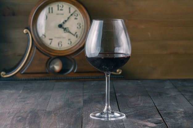 Glass of red wine with clock surface
