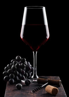 Glass of red wine with dark grapes and vintage corkscrew opener and cork on wooden board on black