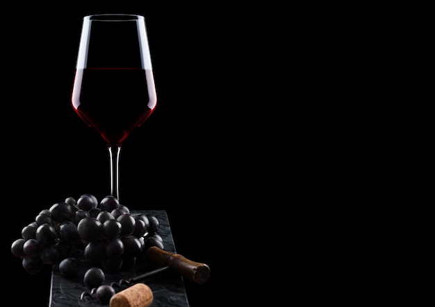 Glass of red wine with dark grapes and vintage corkscrew opener and cork