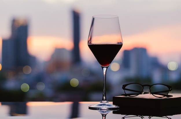 A glass of red wine with glasses and book put on table with city background