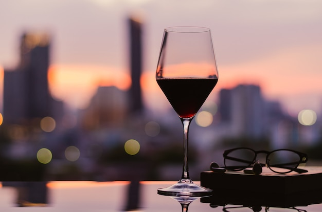 A glass of red wine with glasses and notebook on table with city background