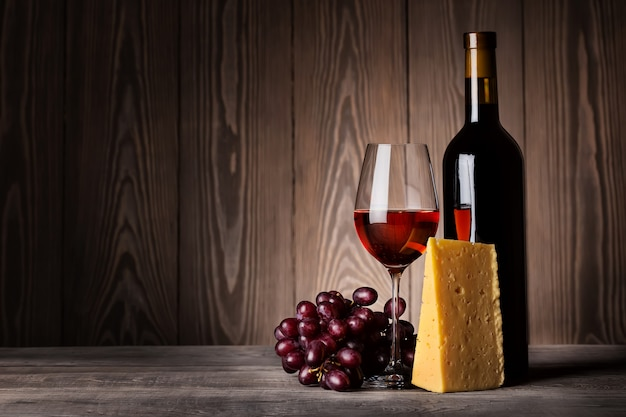 Glass of red wine with grapes and cheese