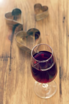 Glass of red wine with hearts on brown wooden table