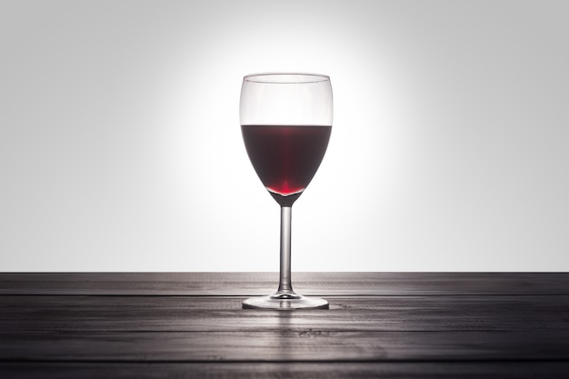 A glass of red wine on a wooden surface