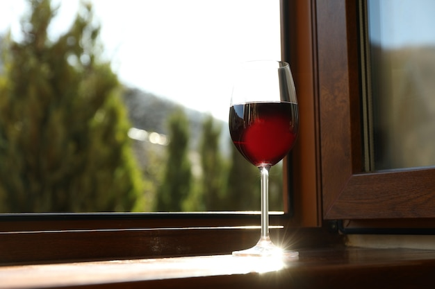 Glass of red wine on wooden windowsill against mountain Premium Photo