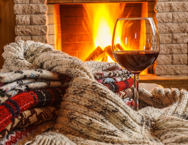 Glass of red wine and wool things near cozy fireplace.