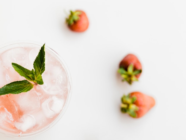 Glass of refreshing cocktail with mint, strawberry and ice