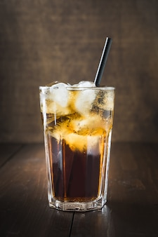 Glass of refreshing cola drink with ice on dark wooden board.