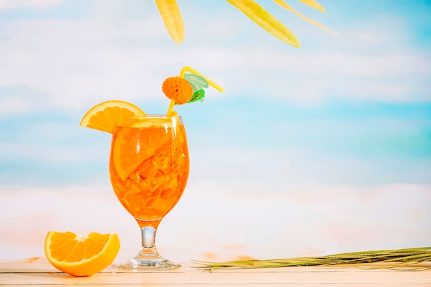Glass of refreshing juicy drink and sliced orange