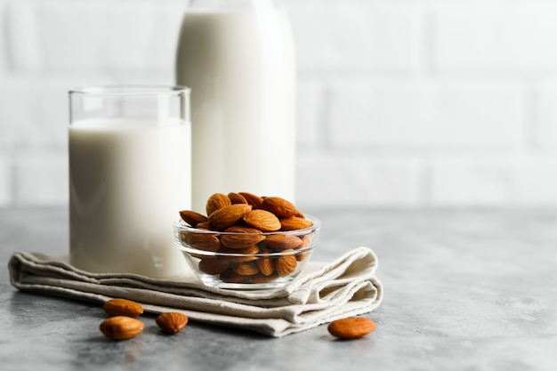 Glass reusable bottle and mug with almond milk and almonds on a marble countertop, kitchen with a white brick wall.