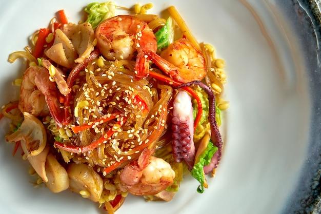 Стеклянная рисовая лапша в кисло-сладком соусе с креветками, гребешками, осьминогами и кальмарами, подается в белой миске