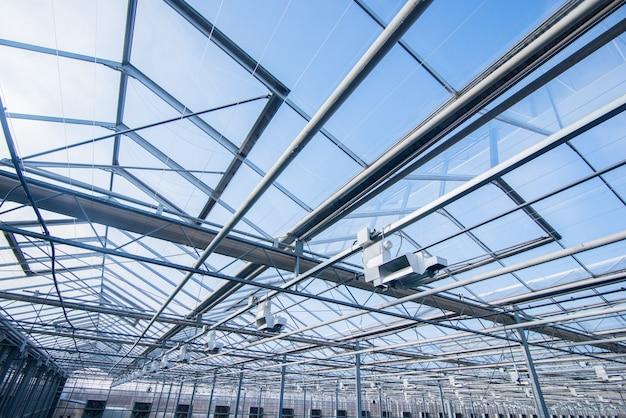현대 온실에 조명 장비가 있는 유리 지붕