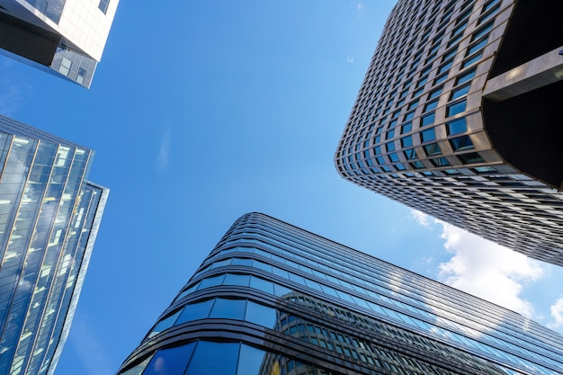 Стеклянные крыши бизнес-центров сфотографированы на фоне голубого неба.