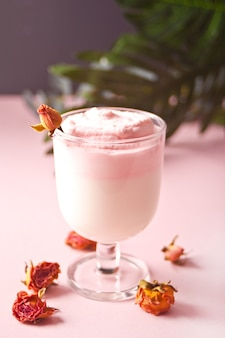 Glass of rose iced dalgona whipped drink coffee.
