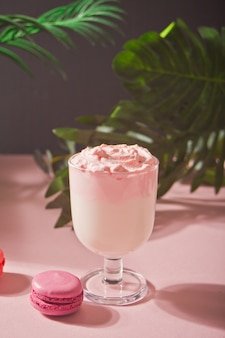 Glass of rose or strawberry iced dalgona whipped drink coffee with orchid for decoration