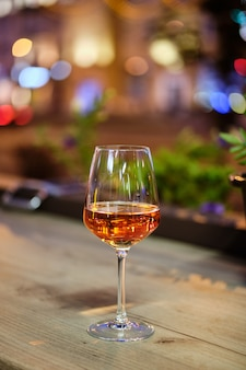 Glass of rose wine on bar counter with night city view