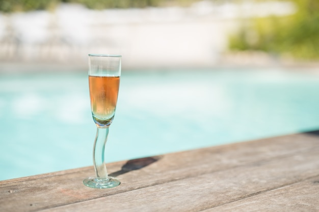 Glass of rose wine at the edge of a swimming pool with a blurred bottom