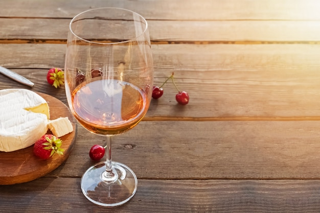A glass of rose wine standing on rustic wooden table with sunset light effect