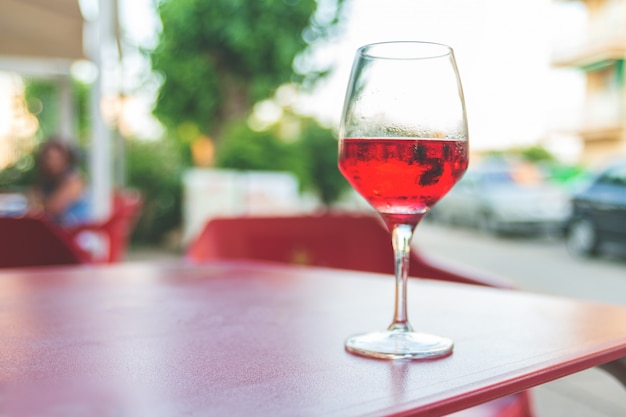 Glass of rose wine on the table in street cafe vintage toning selective focus