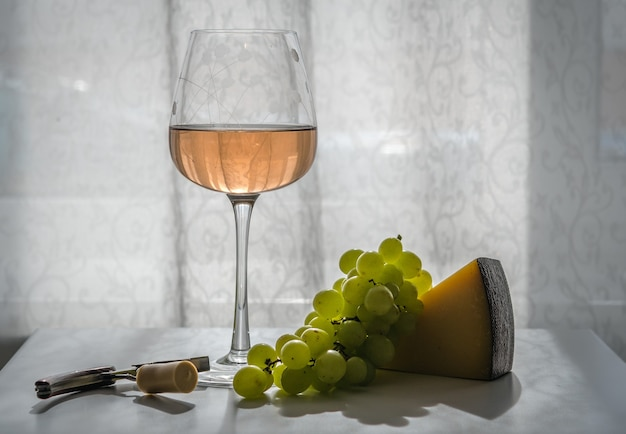 Glass of rose wine on the table in sunny day, next to green grapes, hard cheese, corkscrew with cork. close-up, backlight, horizontal orientation