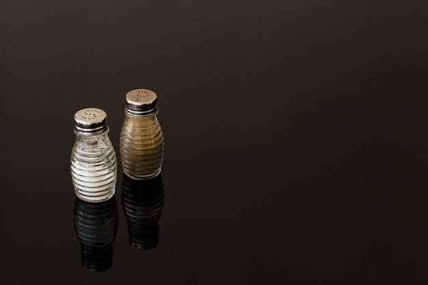 Glass salt and pepper shakers on black background