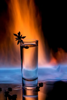 Glass of sambuca on fire with coffee grains and anise star