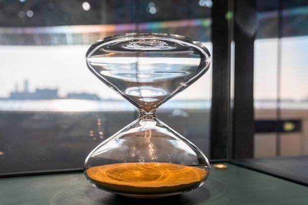 Стеклянные песочные часы с песком внутри. роскошные часы в лувре абу-даби, оаэ.