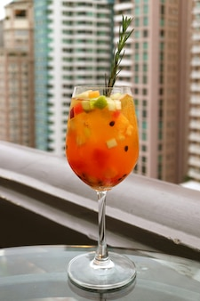 Glass of sangria cocktail with fresh fruits at the roof top bar's terrace