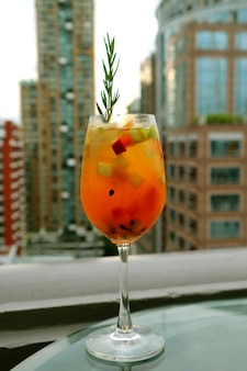 Glass of sangria cocktail with fresh fruits at the roof top bar terrace
