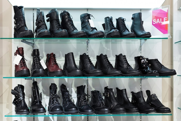 Glass shelves with black man's shoes in a shop