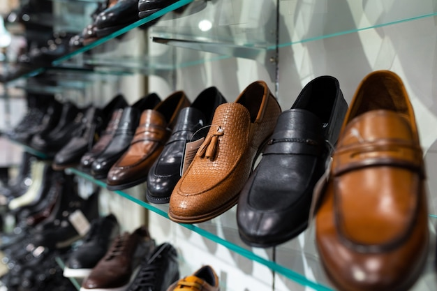 Glass shelves with man's shoes in a shop, focus on shoes