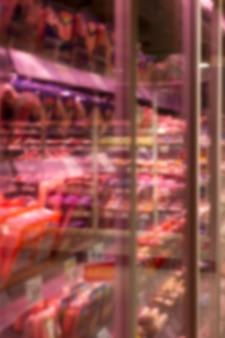 店内に冷蔵肉製品が並ぶガラスのショーケース。垂直。ぼやけた。
